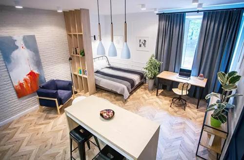 整个空间以冷色调为主,给人一种干净整洁之感。运用白色裸砖墙面及人字拼木地板妆点平米住宅、墙上的印象画加深屋内个性感。